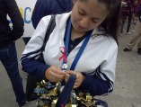 Cheerleader Marcela Velasquez is putting her button on her lanyard. Coach Lora Wsalters gave her, and the rest of the team their buttons.