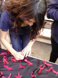 Student Council advisor Gabriela  Dampier is writing her name on the ribbon. She attached the ribbon to the black cloth to pledge to be drug free.