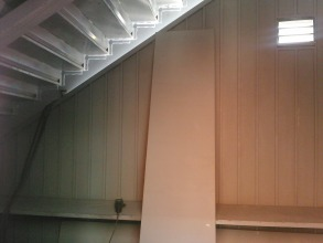 Inside the storage room, under the stairs.