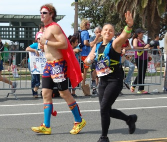 Man in a Superman costume running.