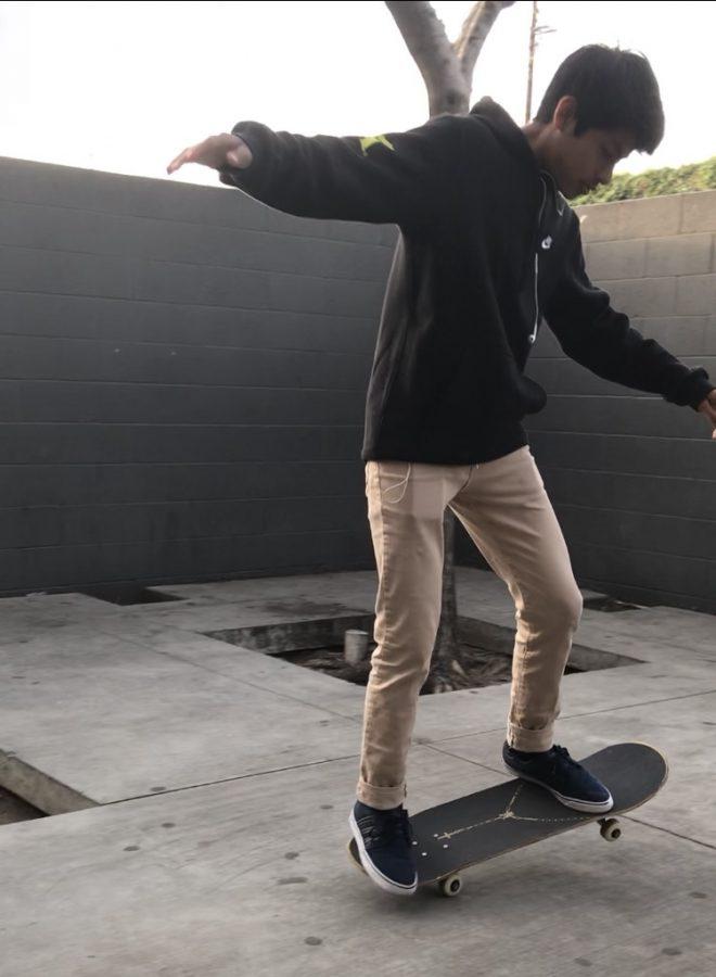 Diego+Aquino%2C+eighth+grade+student+at+AJCMS%2C+skateboarding+on+campus.