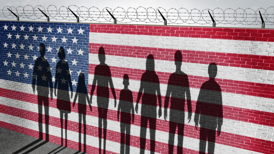 49949787+-+american+immigration+and+united+states+refugee+crisis+concept+as+people+on+a+border+wall+with+a+us+flag+as+a+social+issue+about+refugees+or+illegal+immigrants+with+the+cast+shadow+of+a+group+of+migrating+women+men+and+children.