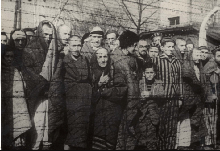 Holocaust survivors standing in front of a barbed wired fence after liberation.